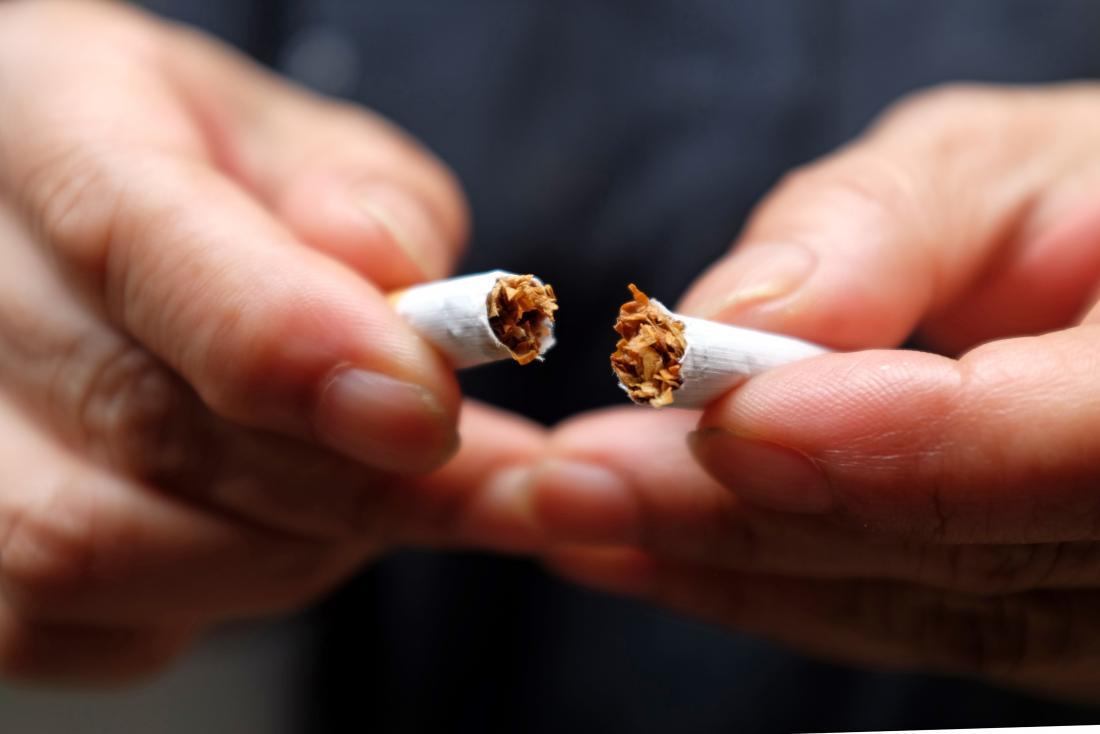 Person ripping a cigarette in half