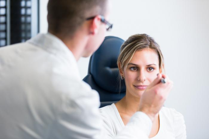 An eye doctor inspects a woman's eyes.