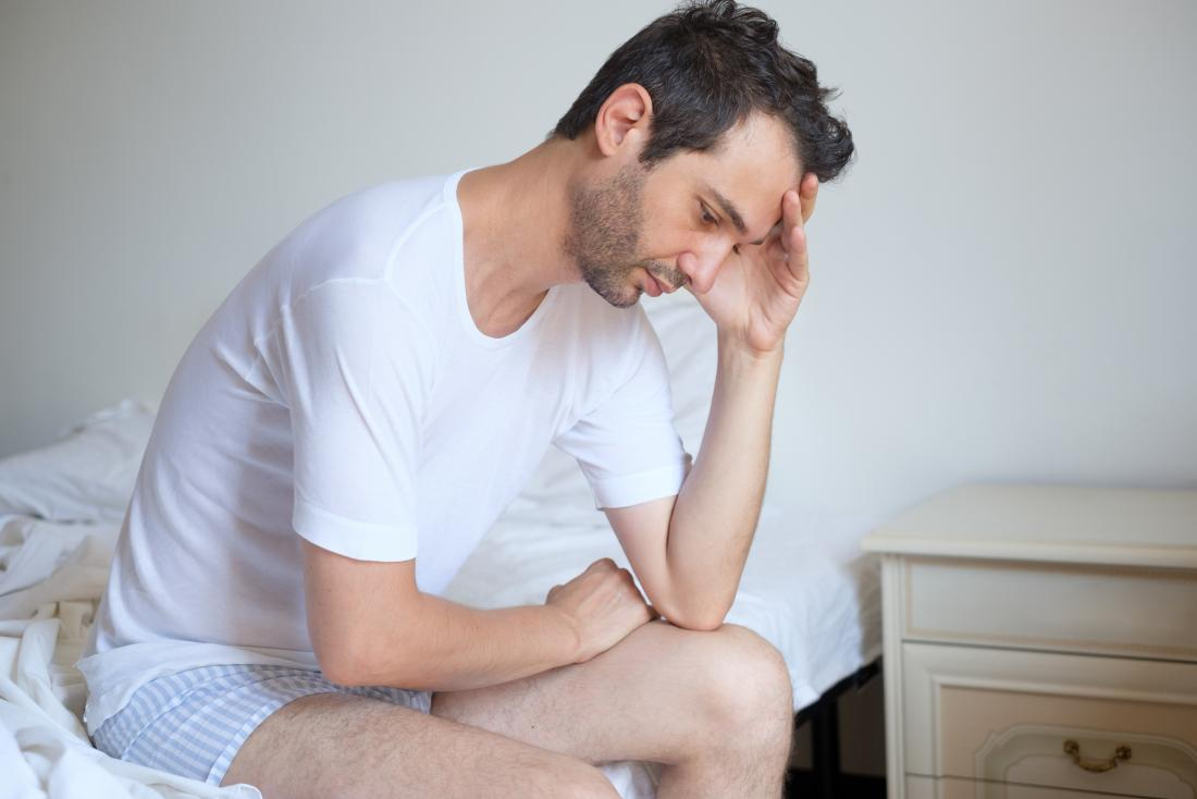 Concerned man with chlamydia and erectile dysfunction (ED) sitting on edge of bed.