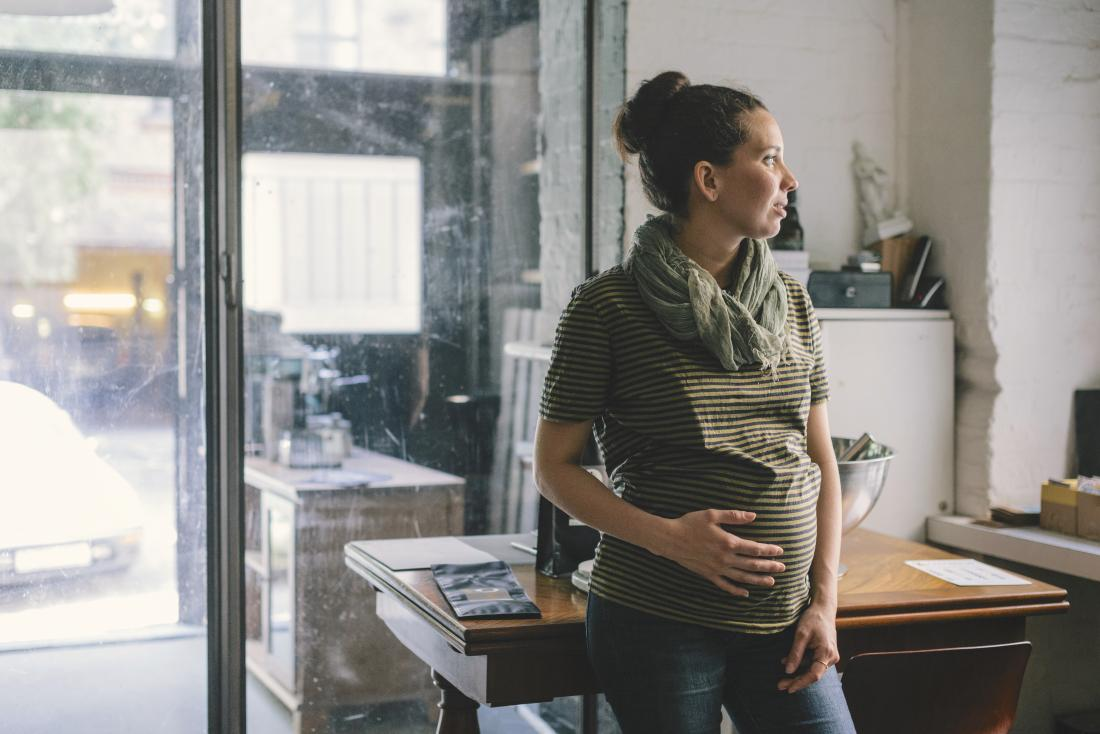 Pregnant woman with Crohn's holding belly