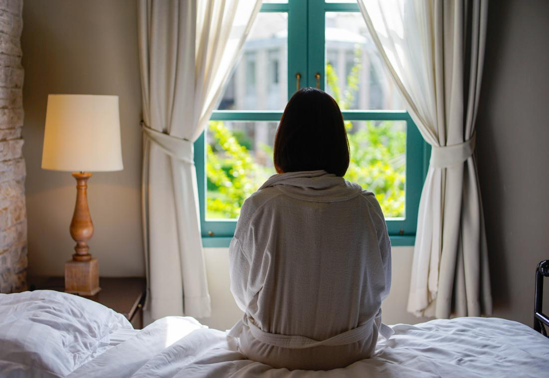 woman sitting on the edge of the bed seen from behind