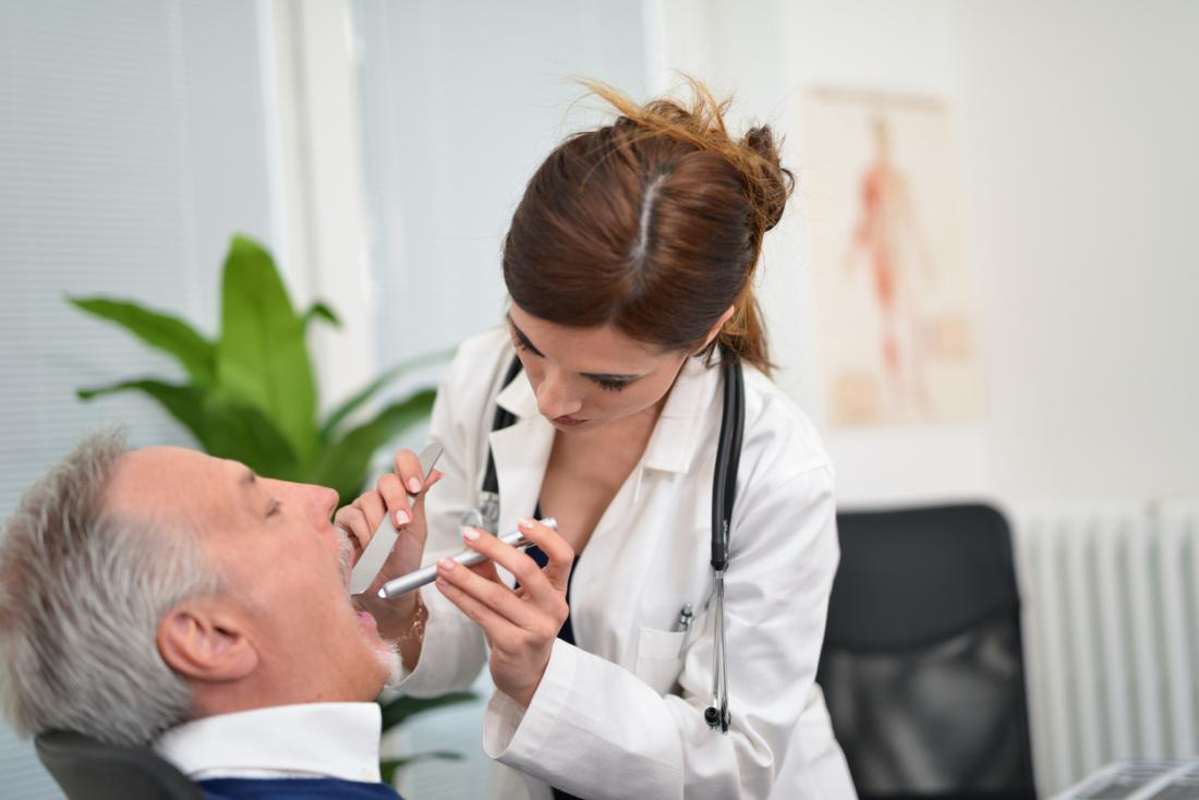 Dentist inspecting patient's teeth and mouth.