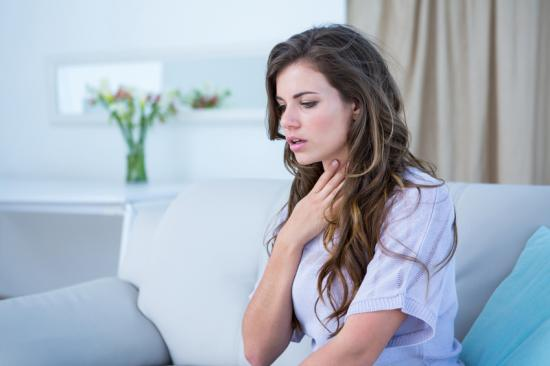 Woman experiencing shortness of breath holding her chest