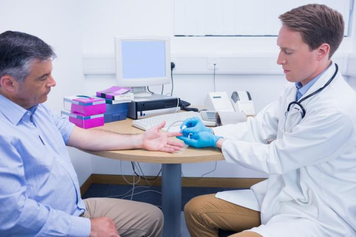 A doctor checks the blood sugar levels of a man.
