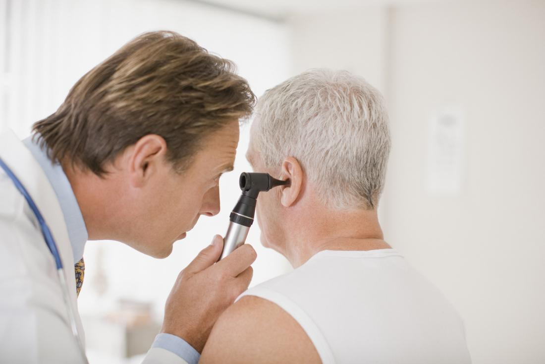 Doctor performing an ear exam on a senior male patient.