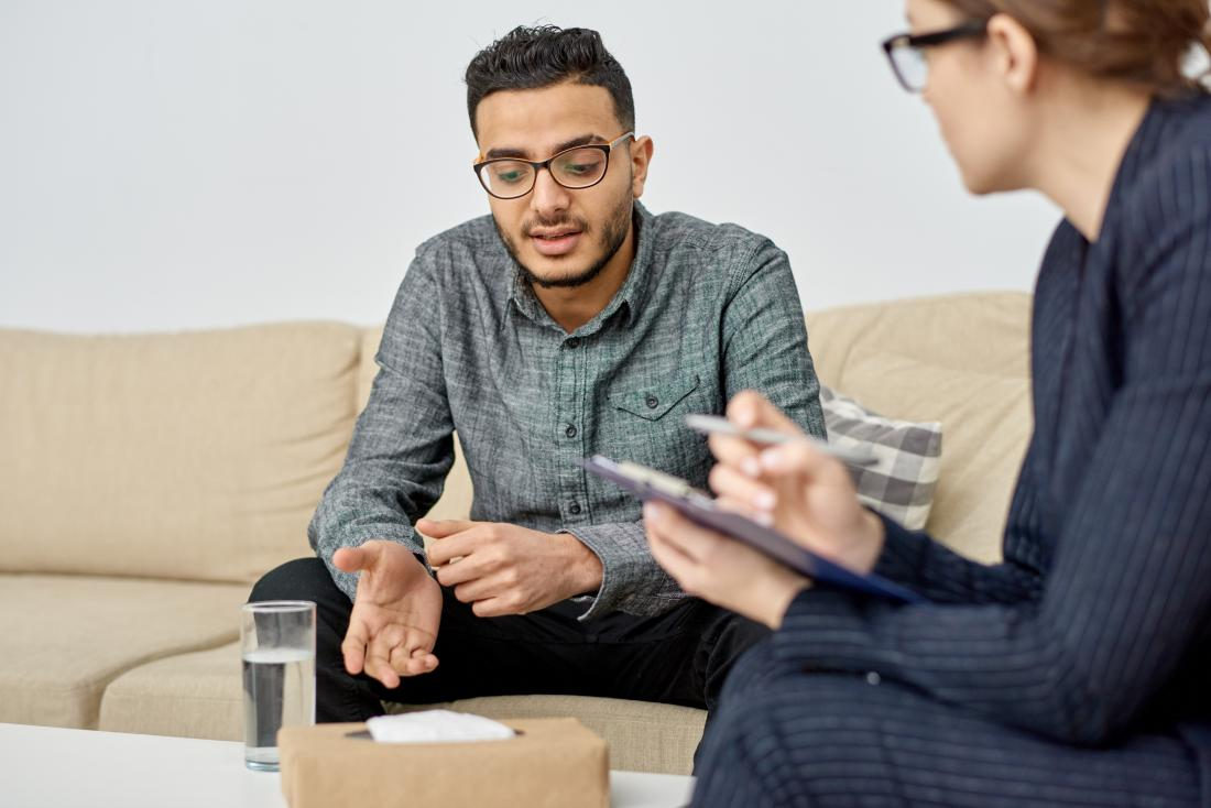 Young man in therapy session speaking to counselor during psychotherapy