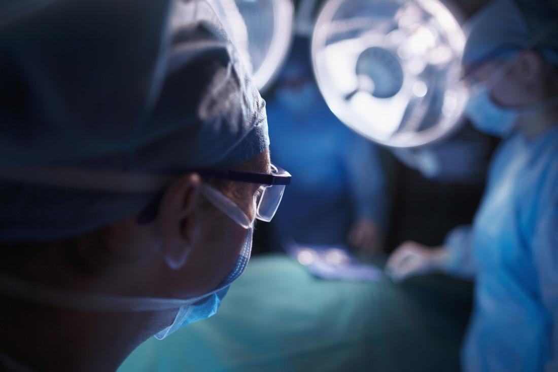 Surgeons working in operating room, silhouette of surgeon wearing glasses and mask in foreground.