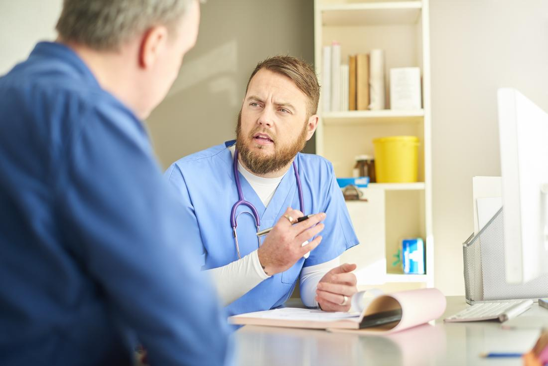 Doctor speaking to patient in office.