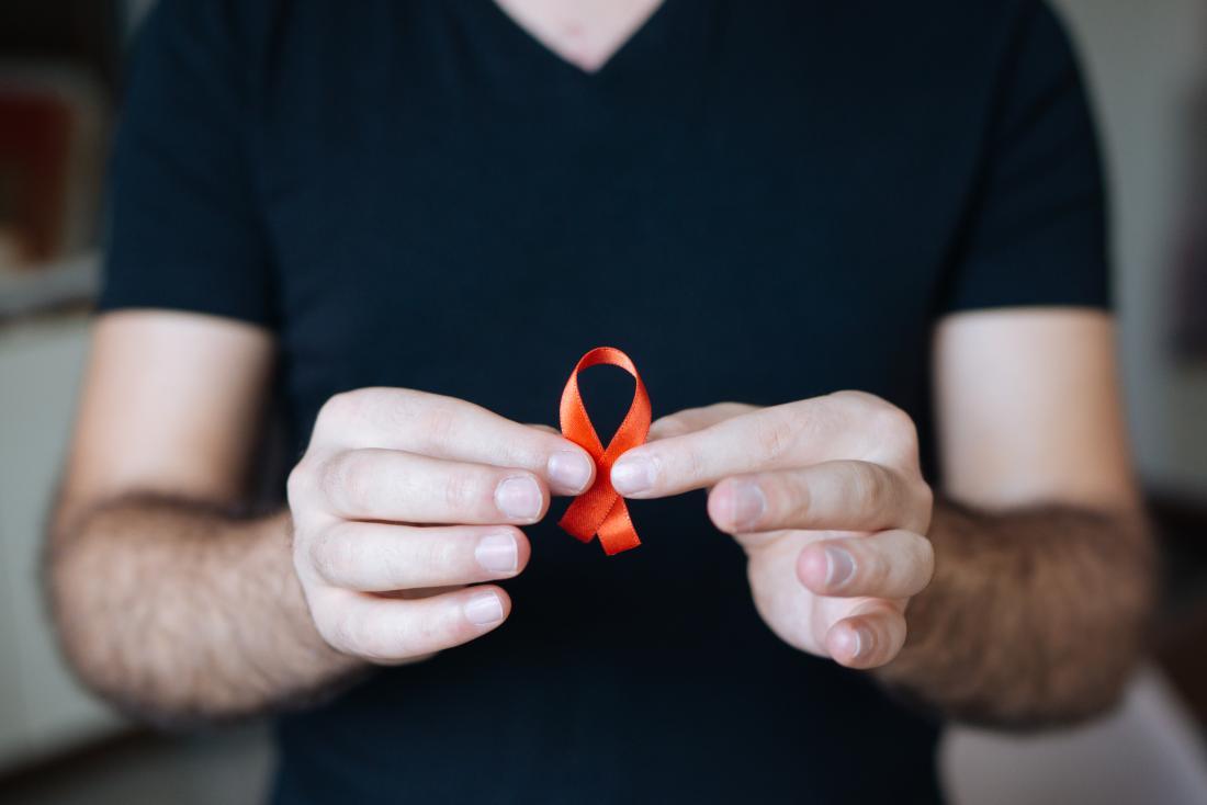 Man holding up red HIV awareness ribbon