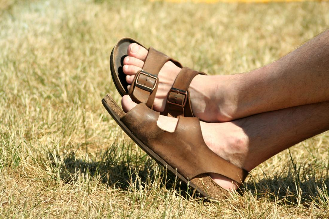 Men's open heel and toe sandals or soft shoes on grass.