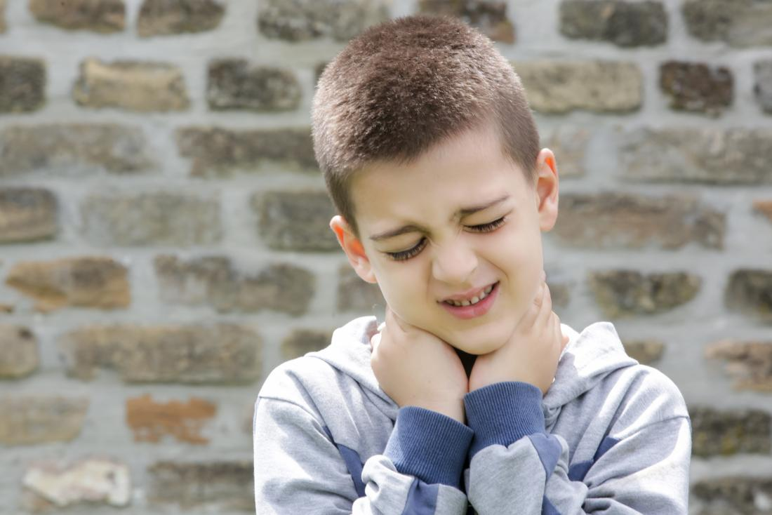 young boy holding his neck in pain