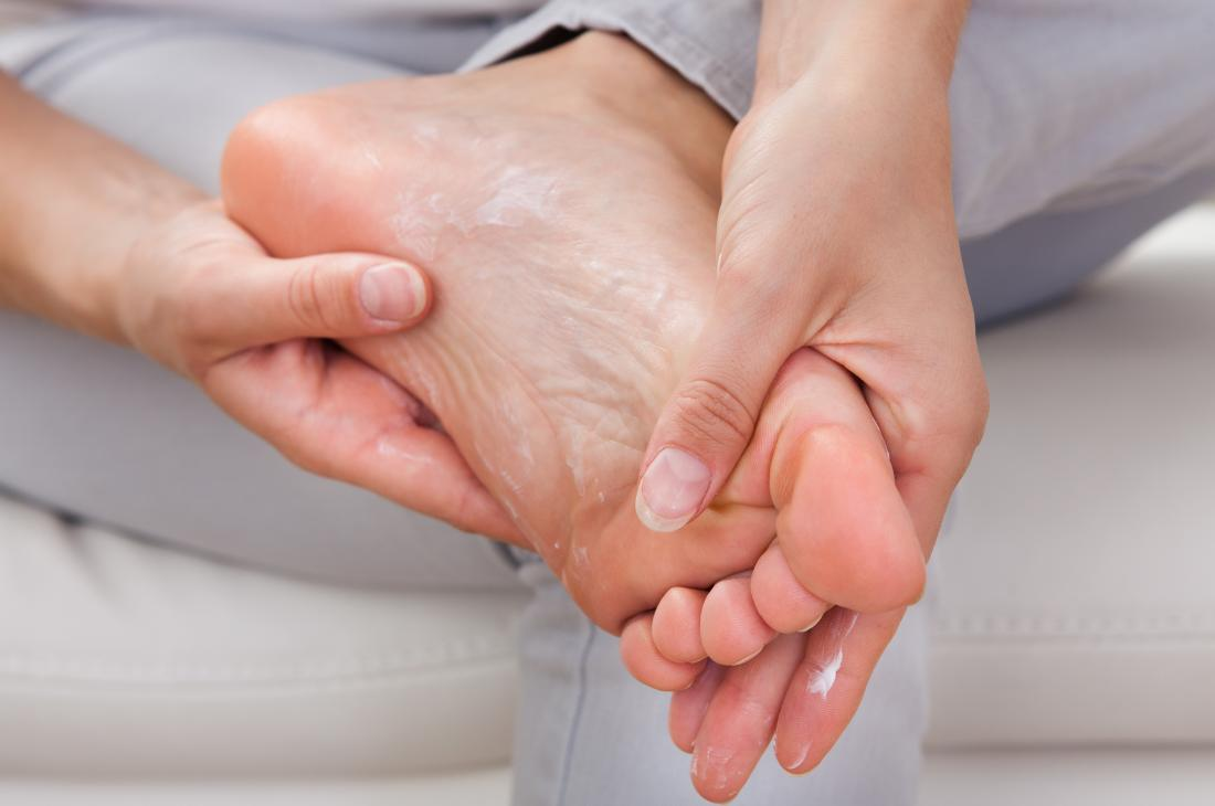 Woman applying moisturizing lotion to her feet.