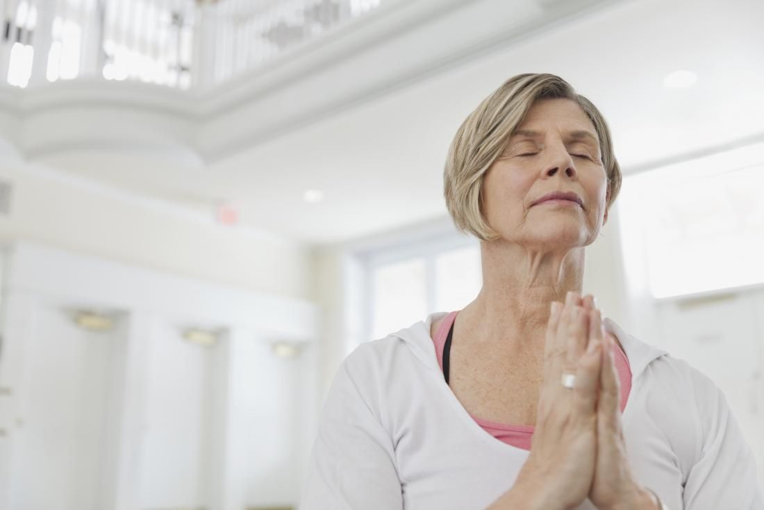 Mature woman doing yoga and meditation with breathing exercises.
