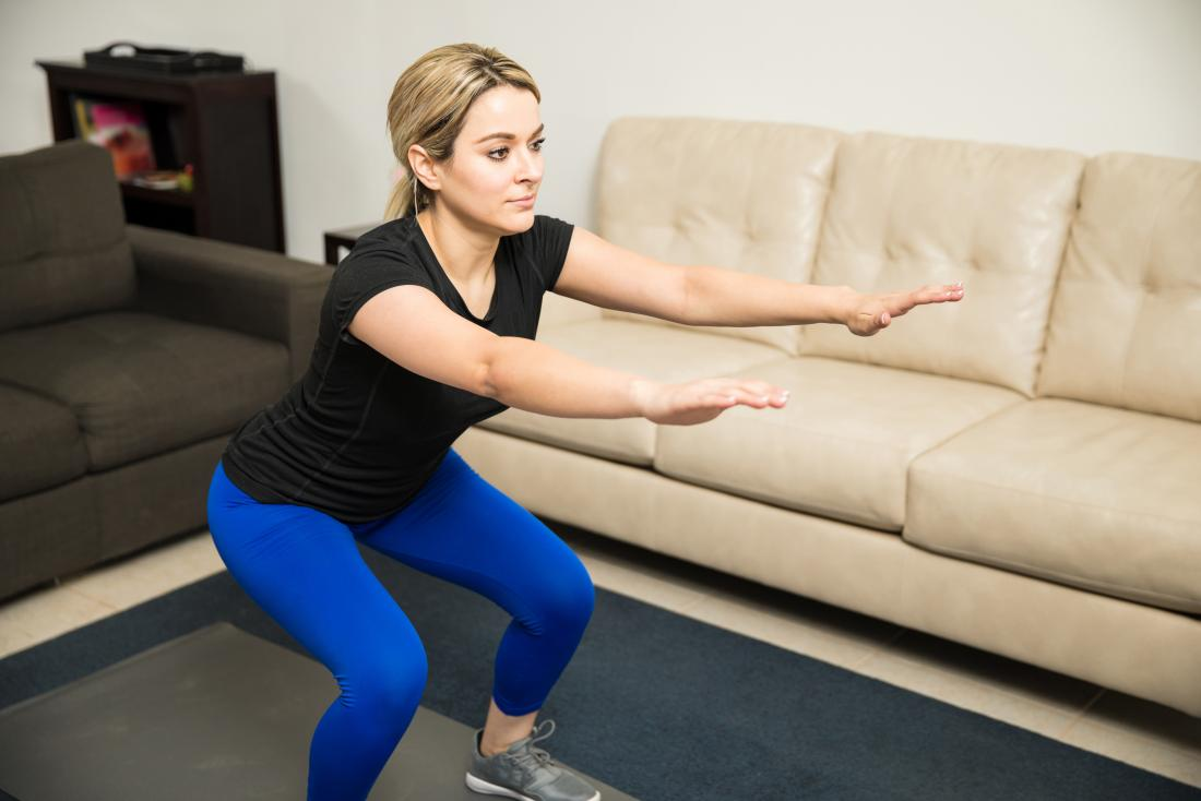 Woman doing a squat in her living room