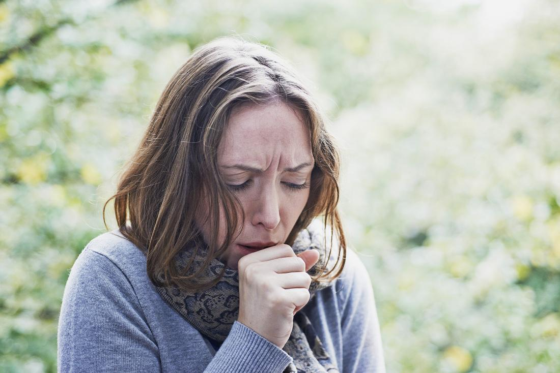 Woman outdoors with flu or cold infection coughing