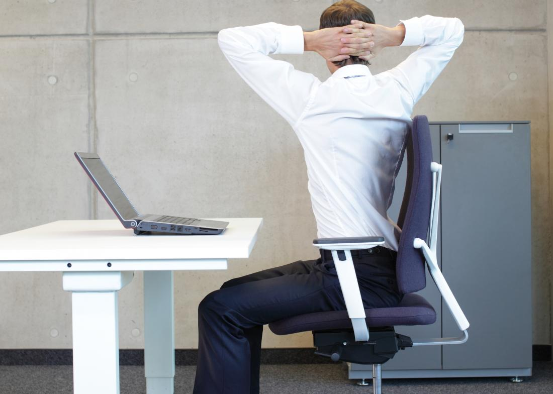 Person seated on chair at desk doing back twist stretches