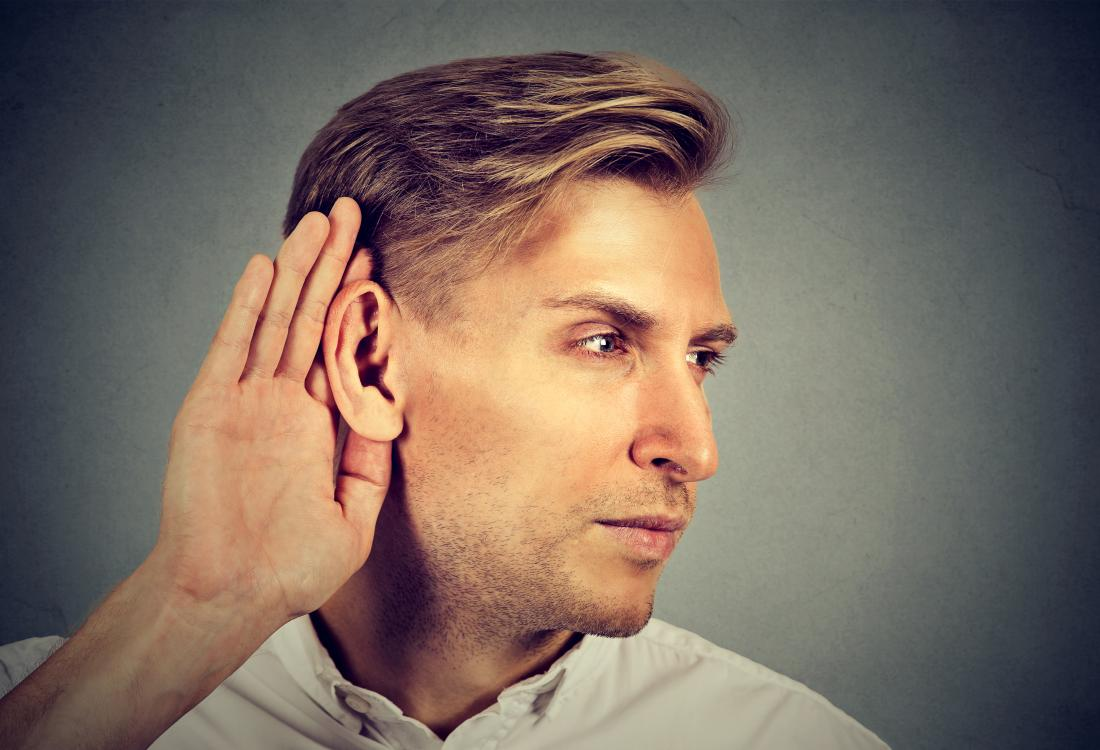 man cupping his ear