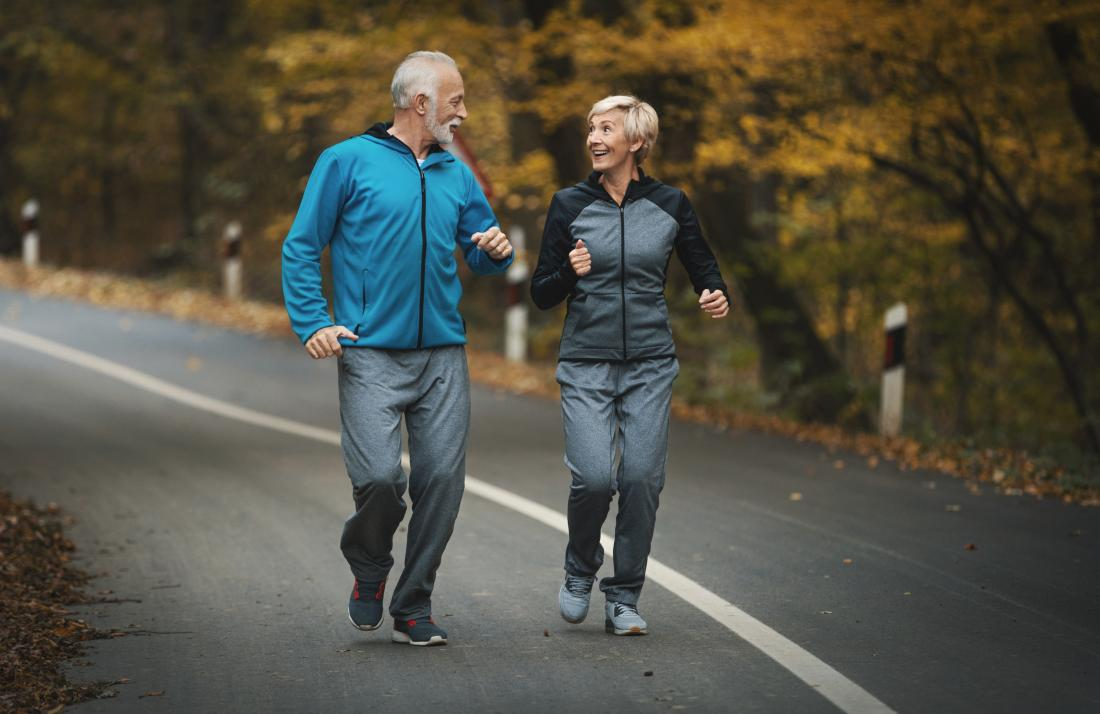 Senior couple smiling outdoors jogging.