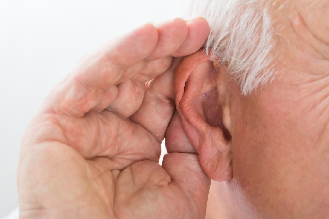 an older man with his hand by his ear