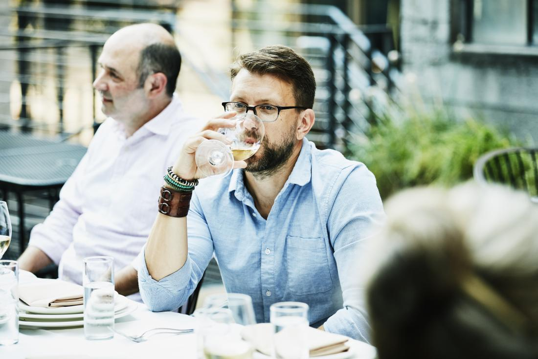Man drinking beer outdoors at dining table