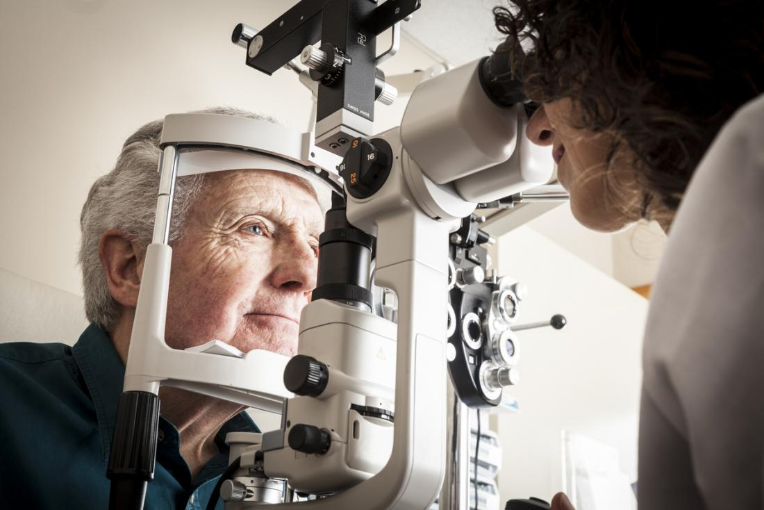 Mature male patient having eye exam at optometrist.