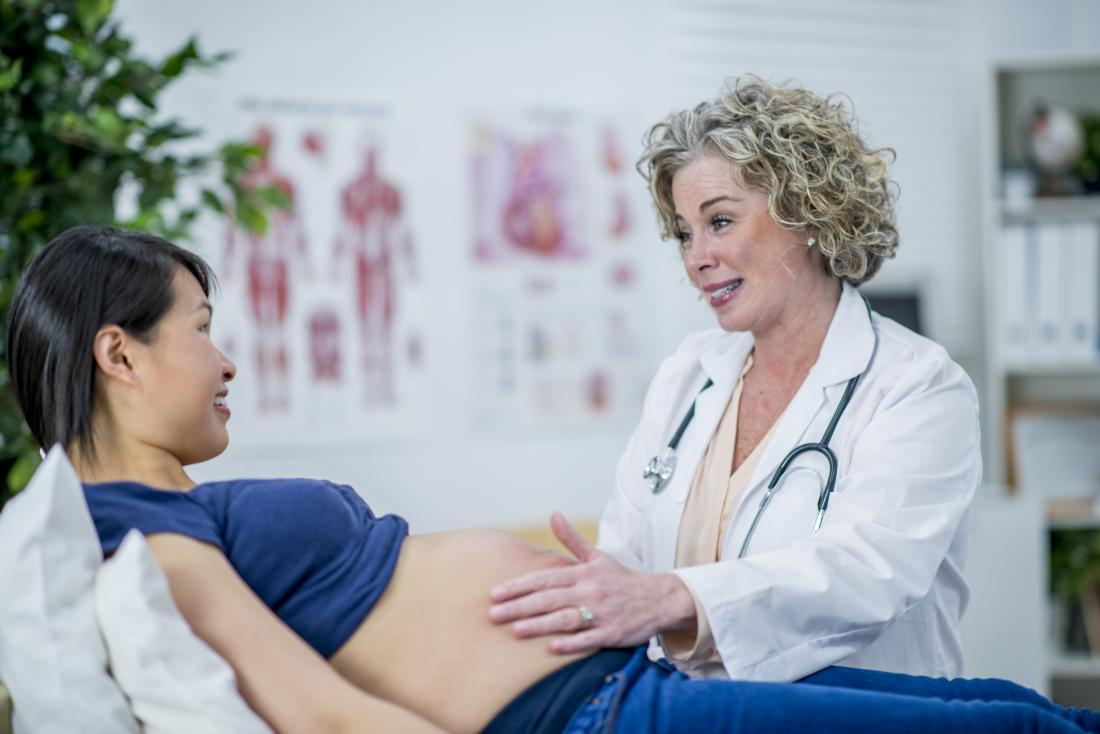 Pregnant woman in second trimester visiting with her doctor