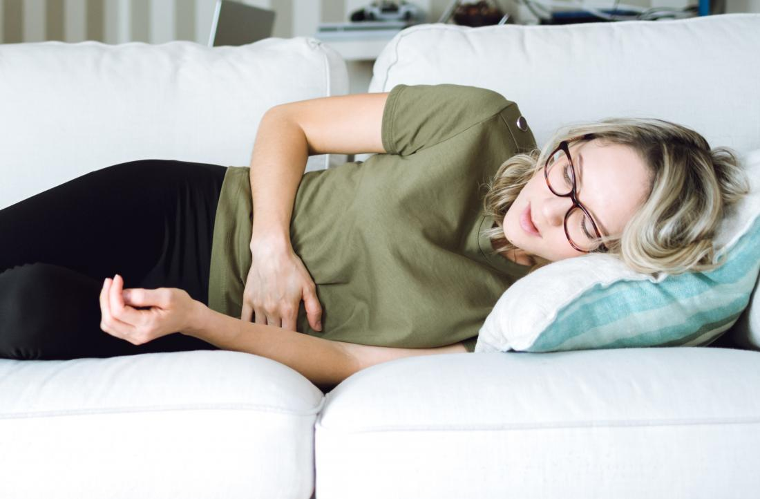 woman lying on side with stomach pain.