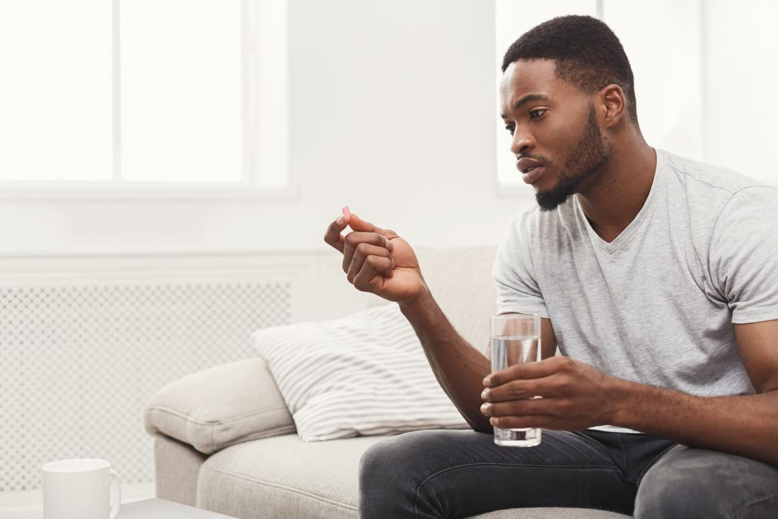 Man holding glass of water and pill taking medication.
