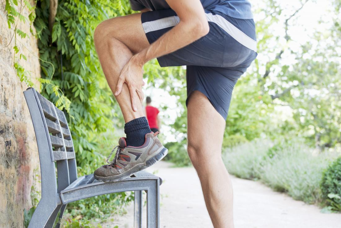 soleus strain causing calf pain in person outdoors in running clothes with leg on bench holding calf.