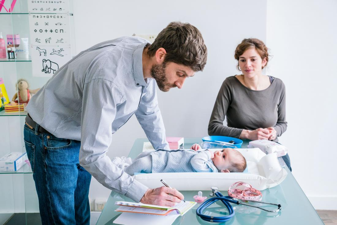 Doctor assessing baby in pediatrician office.