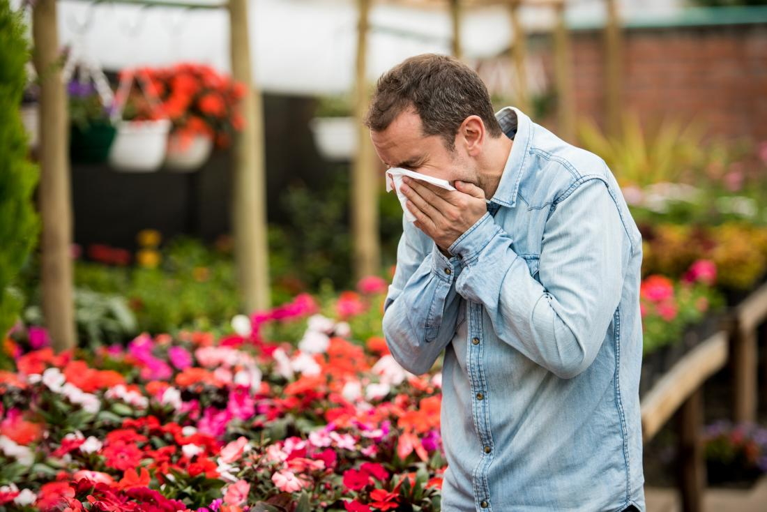 man standing by flowers and sneezing