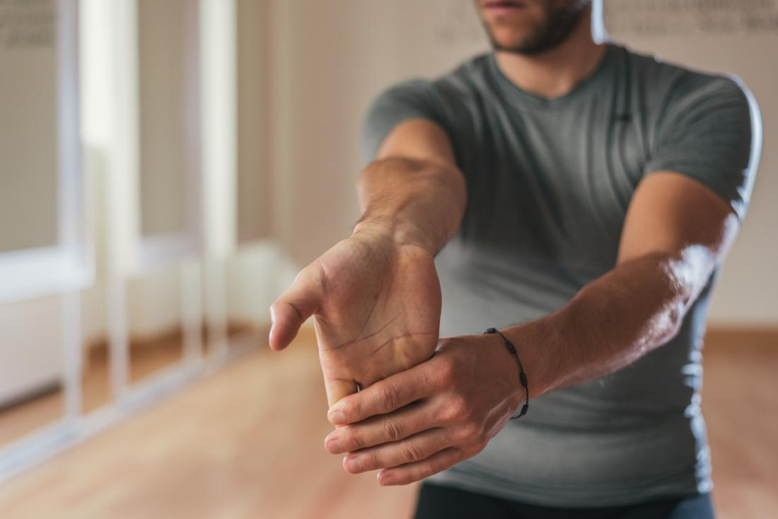 Man stretching his hand and forearm