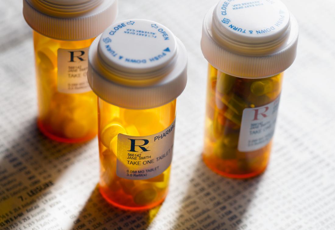 Prescription medicine bottles on paperwork with pills.