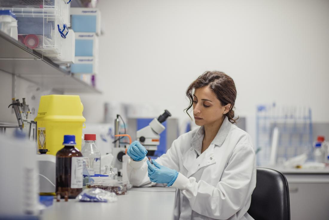 Lab technician examining sample of blood in vial