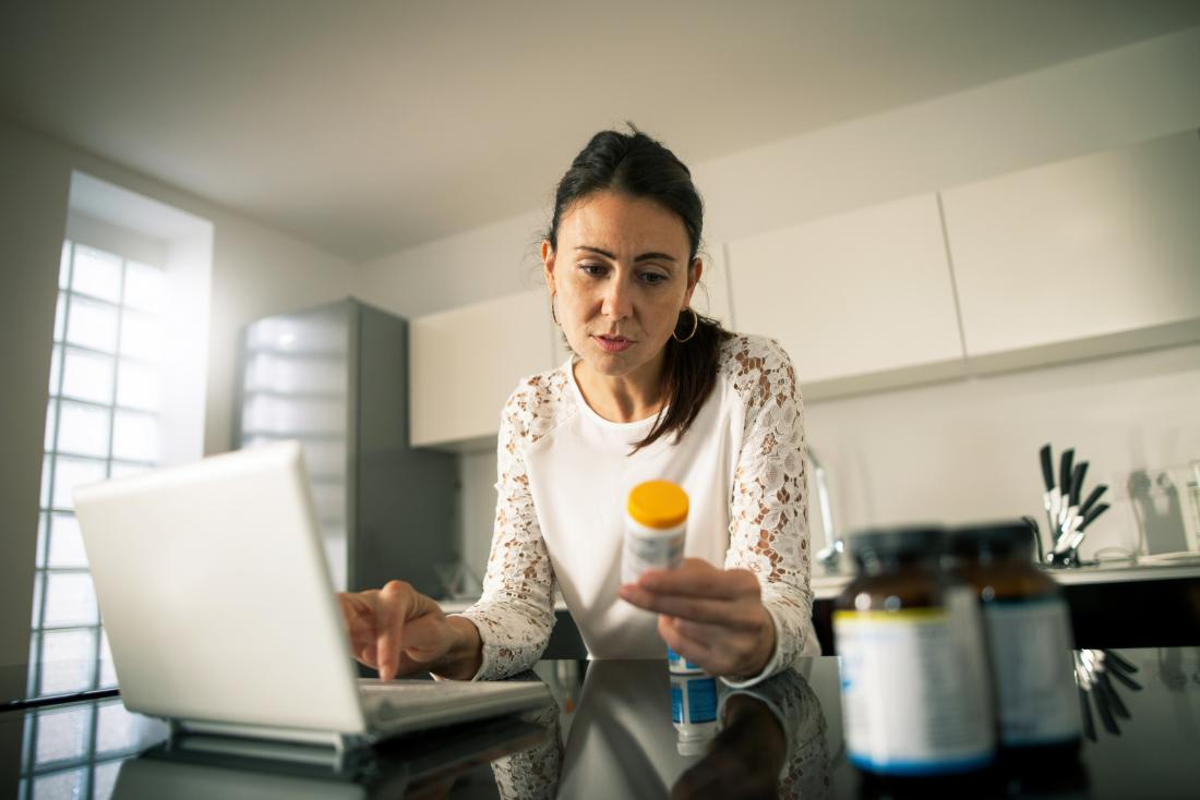 Woman in kitchen on laptop holding prescription pill bottle and reading label