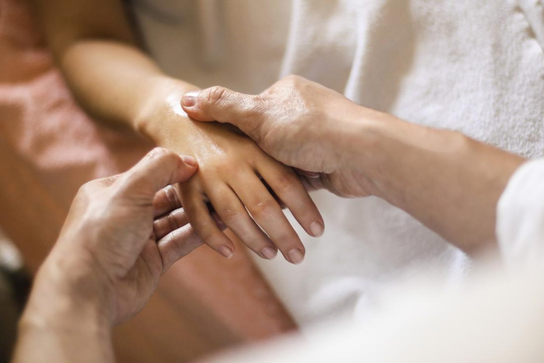 Acupressure therapy being applied to persons hand and wrist.