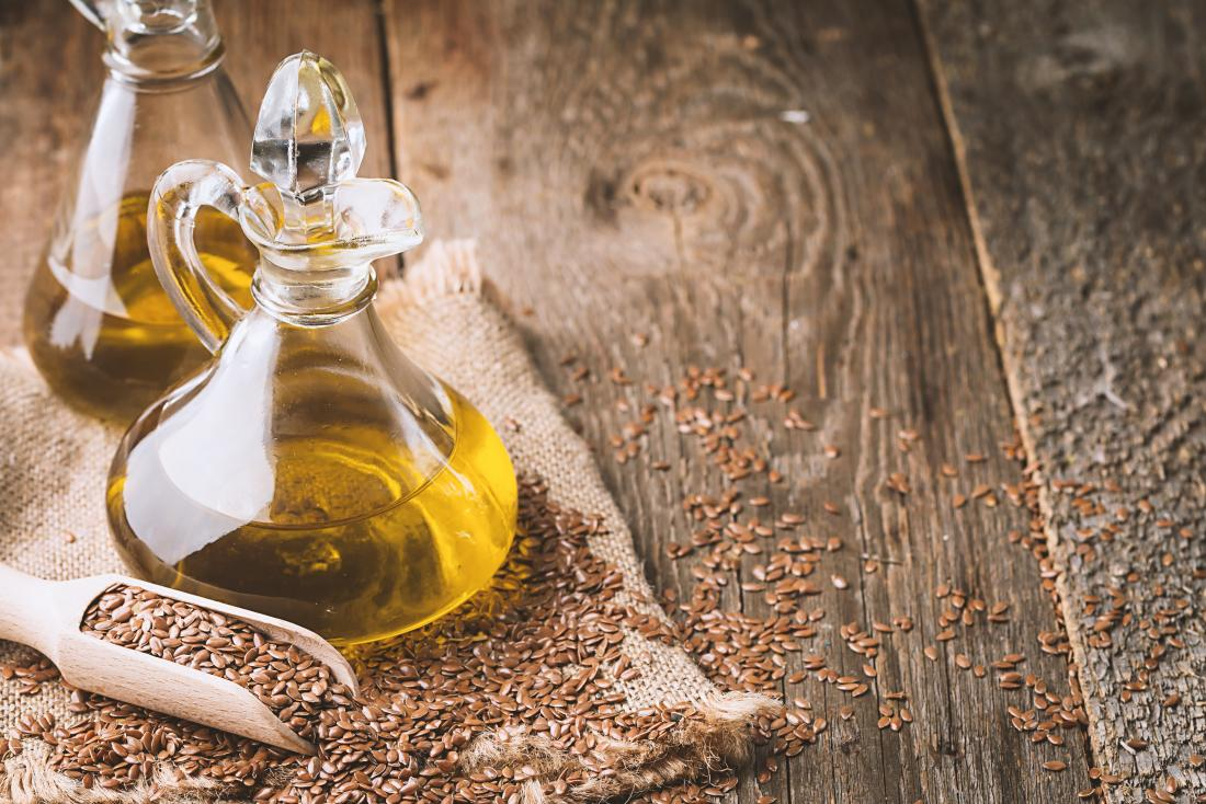 Flaxseed oil and linseed on a wooden bench