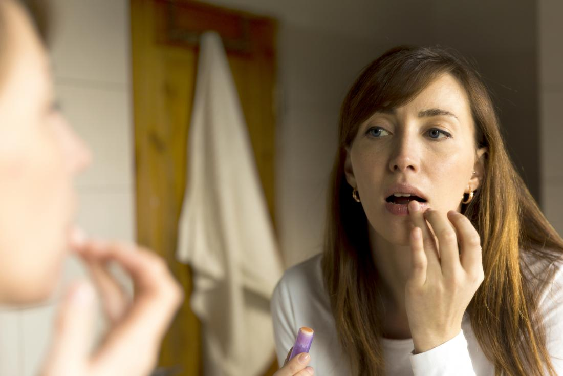 Woman applying lip balm to dry or chapped skin in front of mirror