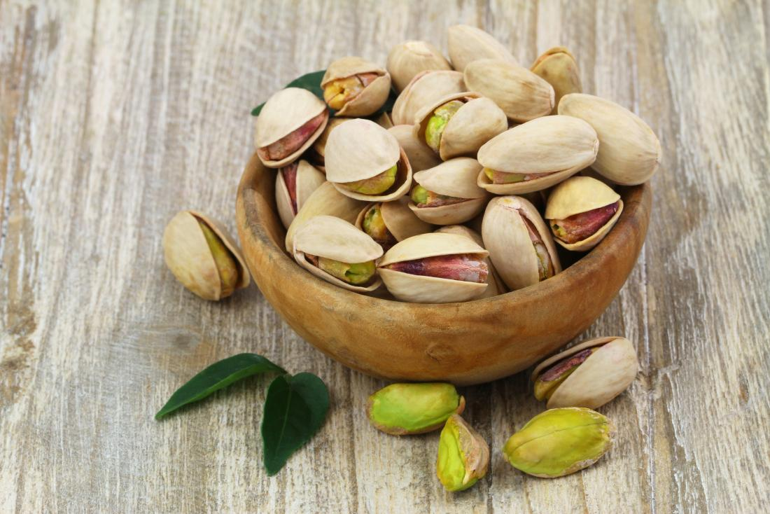 Pistachio nuts in a bowl in and out of shells