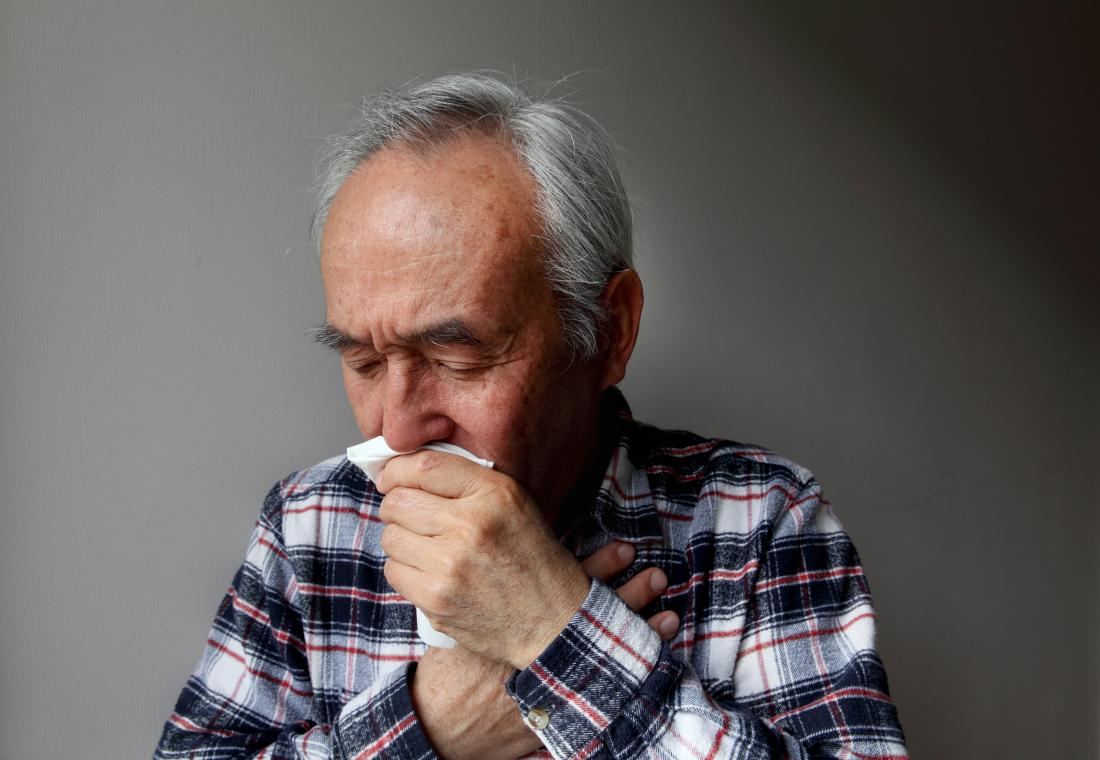 Senior man with COPD coughing into tissue.