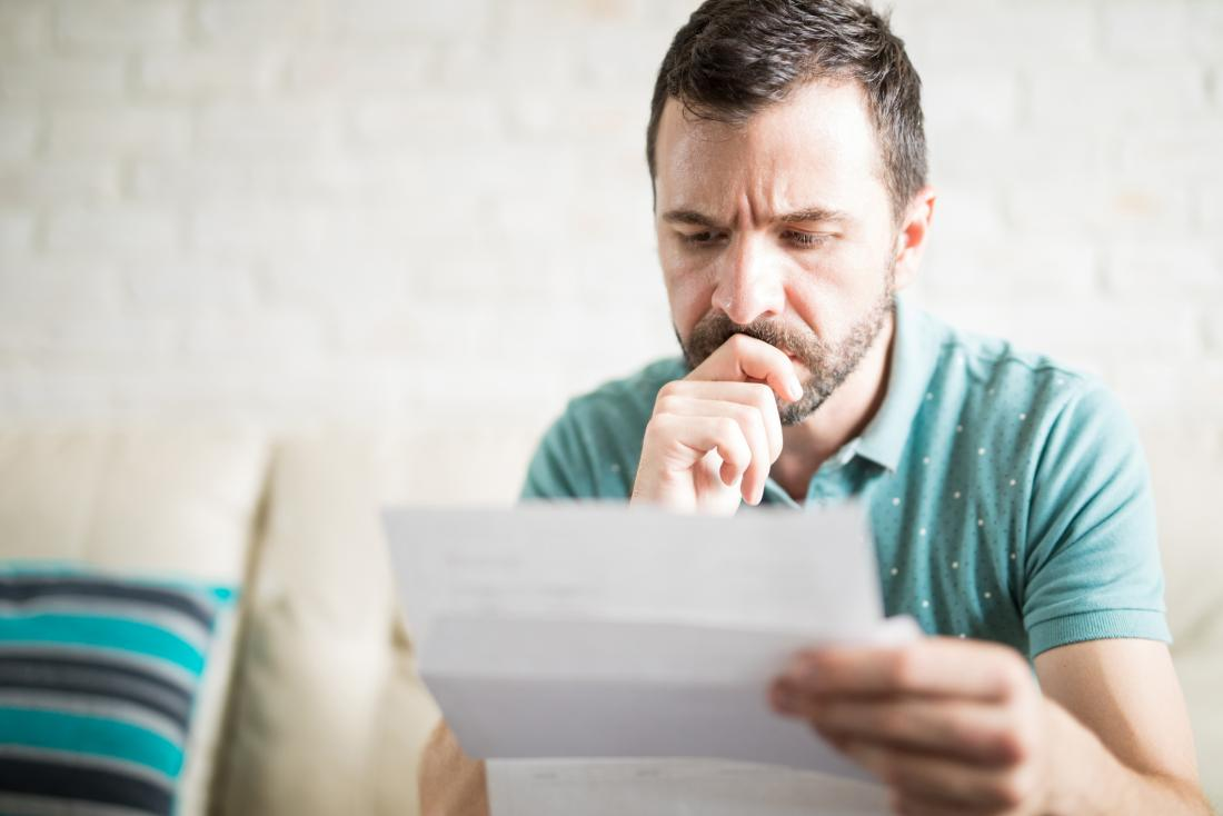 Man reading letter and worrying about signs of lung cancer in men