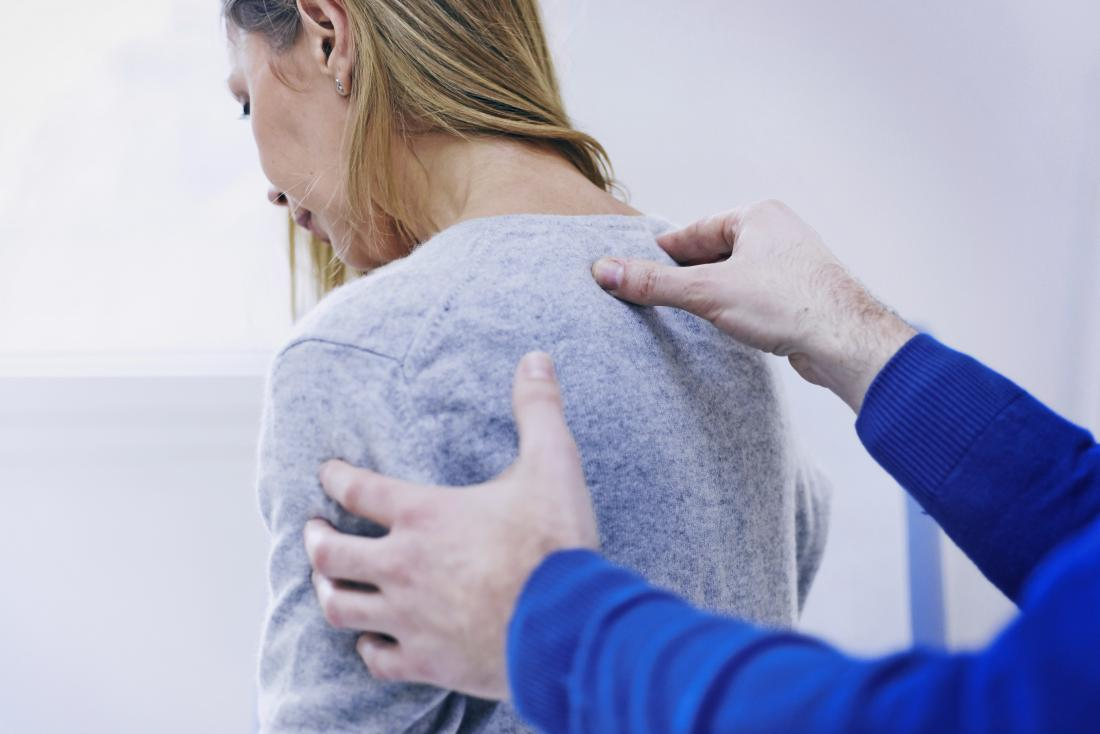 Woman with upper back, shoulder and neck pain at chiropractor or physical therapists