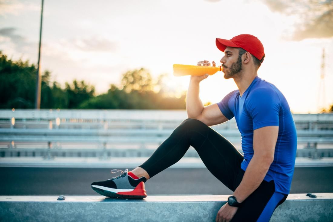 Athlete drinking sports energy drink after exercising.