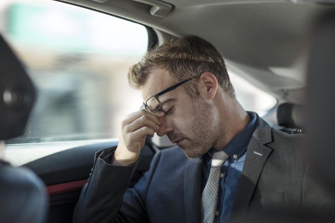 Tired and fatigues businessman in back of tax or car rubbing bridge of nose under glasses because of stress and exhaustion