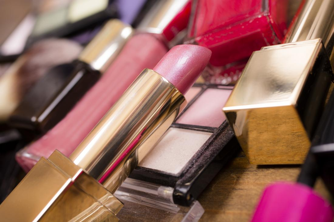 Cosmetics piled on table, including lipstick and lip gloss as well as eye shadow