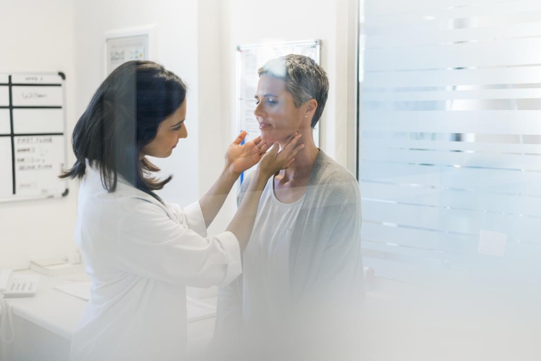 Doctor checking female patients thyroid glands