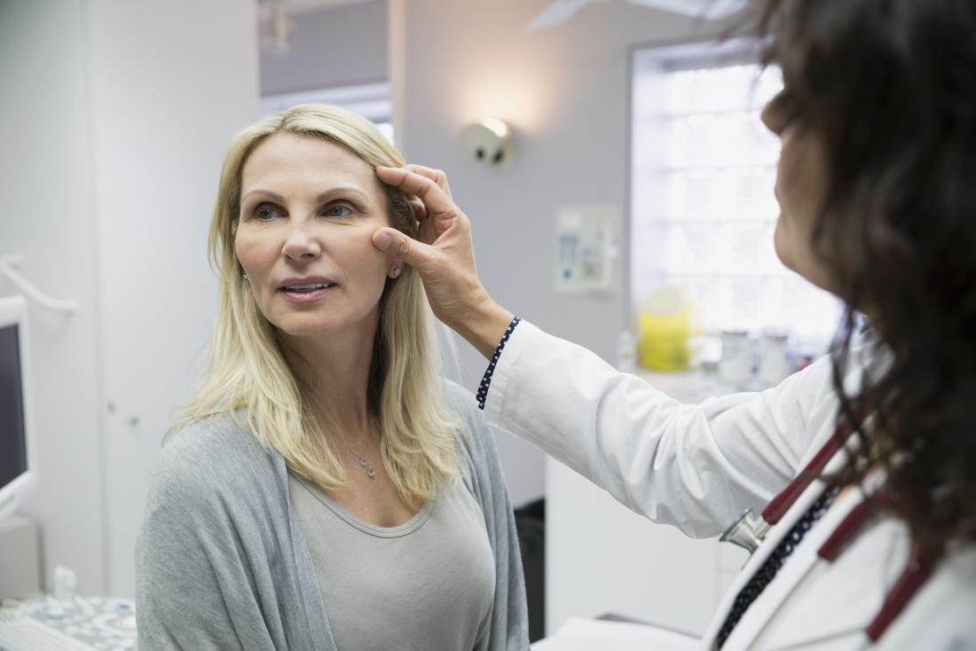 Doctor inspecting womans face