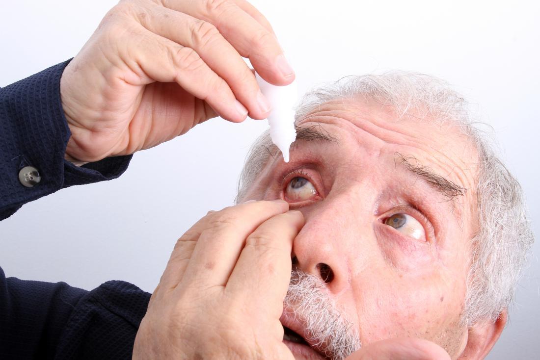 senior man applying eye drops because of burning eyes