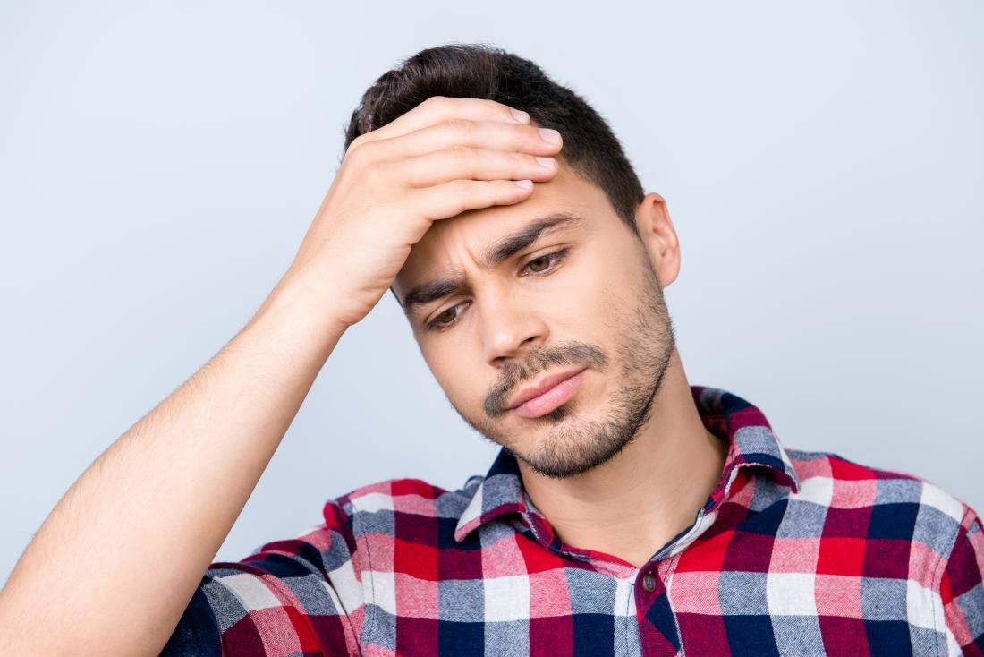 Man with headache on top of head holding forehead in pain.