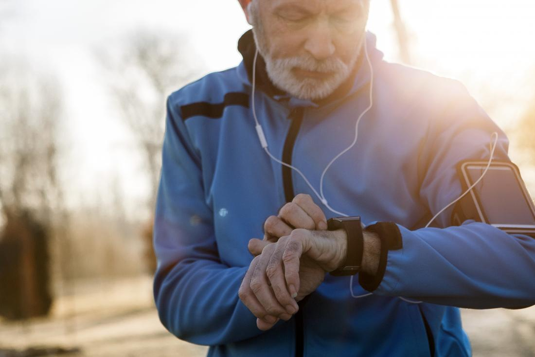 Man looking at watch during interval training.